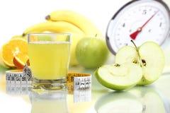 Le jus de pomme en verre, échelles de mètre de fruit suivent un régime la nourriture Photographie stock libre de droits