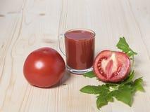 Le jus de tomates rouge de tomate et la tomate demi sur la tomate part Photo stock