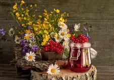 Le jus des baies du viburnum dans des récipients en verre sur une serviette à côté d'un bouquet des fleurs sauvages sur un suppor image stock