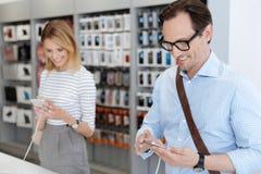 Le köpande smartphones för folk på elektronik shoppa royaltyfri foto
