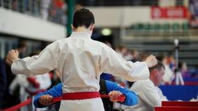 Le karaté badine des concours - kimono de port de combattant d'adolescent d'aides d'entraîneur banque de vidéos