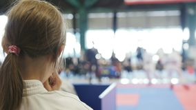 Le karaté d'adolescent folâtre la fille regardant pour combattre sur le tatami - spectateur - concurrence de karaté banque de vidéos