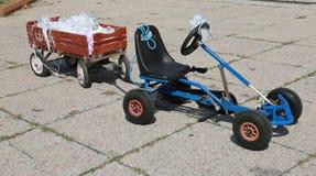 Le kart de pédale avec un chariot avec des flocons a collé à la jeune mariée et au gro photos stock