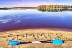 Le kayak barbote la pose sur la plage de lac près de l'été de mot écrit sur le sable Images libres de droits