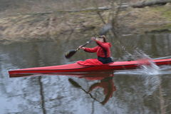 Le kayak rouge flotte le long de la rivière en premier ressort photos stock