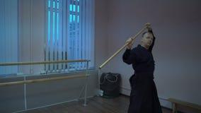 Le kendo principal aiguise des réceptions avec un matin en bois d'épée dans le hall de formation clips vidéos
