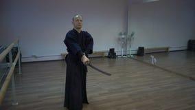 Le kendo principal balance par l'épée katan du ` s, trains fait le kata dans la salle de gymnastique avec des miroirs banque de vidéos