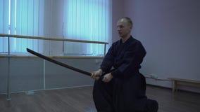 Le kendo principal dans le kimono exécute des exercices avec l'épée dans la fierté de Halloween clips vidéos
