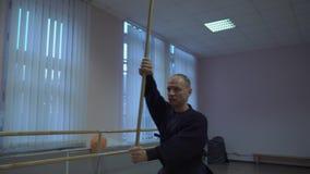 Le kendo principal exécute le kata avec le bâton en bois, s'exerce dans le hall tôt le matin banque de vidéos