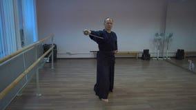 Le kendo principal exécute le kata avec l'épée de katana dans le hall de formation avec des miroirs banque de vidéos