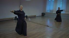 Le kendoka principal exécute le kata dans la salle de gymnastique avec des miroirs, fait la chute avec l'épée katan banque de vidéos