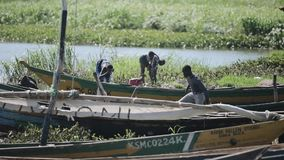LE KENYA, KISUMU - 20 MAI 2017 : Jeune homme africain préparant son bateau avant travail Les gens prenant la douche dans le lac banque de vidéos