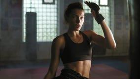 Le kickboxer femelle sportif fort frappe un sac de boxe avec sa jambe Elle s'exerce avec un sac de boxe dans le gymnase foncé ave banque de vidéos