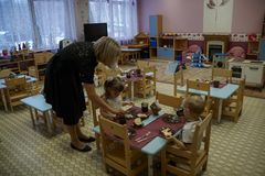 Le Kindergartener aide des enfants à manger Peu garçon et fille mangeant le petit déjeuner au jardin d'enfants images stock