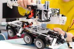 Le kit d'ensemble de voiture, femme assemblent un jouet très compliqué et commun de camion de voiture photographie stock