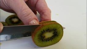 Le kiwi de tranche de mains sur le blanc préparent la nutrition clips vidéos