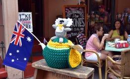 Le koala de Knitten se reposant sur un jaune et vert knitten la théière confortable Photographie stock