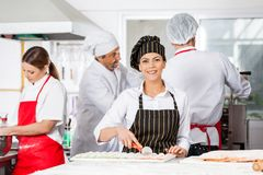 Le kocken Cutting Ravioli Pasta med kollegor arkivbild