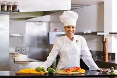 Le kocken med klippta grönsaker i kök Royaltyfri Fotografi