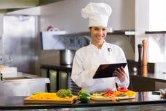 Le kocken som använder den digitala minnestavlan, medan klippa grönsaker Royaltyfria Bilder