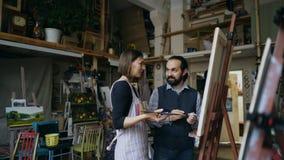 Le konstnären man undervisningunga flickan för att dra målningar och förklaring av grunderna i konststudio Royaltyfria Bilder