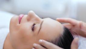 Le koppla av kvinnan som tycker om och har bra tid på massagesalongen under tillvägagångssättnärbild arkivfilmer