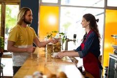 Le kunden som betalar räkningen vid kassa på räknaren Royaltyfri Foto