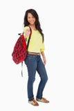 Le kvinnadeltagarethumb-up med en ryggsäck Arkivfoto