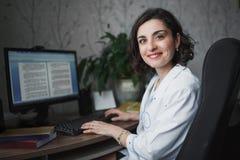 Le kvinnadoktorn i ett vitt medicinskt ämbetsdräktsammanträde på en tabell På tabellböckerna, en datorbildskärm och en grön växt  royaltyfria bilder