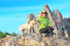 Le kvinnahandelsresanden och vit dog sammanträde på stenar som kopplar av med Rocky Mountain Royaltyfri Fotografi