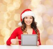 Le kvinnan i den santa hatten med gåva- och minnestavlaPC Royaltyfri Fotografi