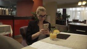 Le kvinnan i exponeringsglas genom att använda mobiltelefonen på bakgrundsinrekafét stock video