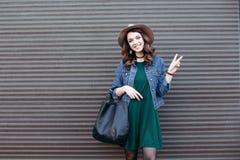 Le kvinnan i gatablickstil som gör en gest fred och posera fotografering för bildbyråer