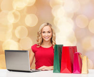 Le kvinnan i röd skjorta med gåvor och bärbara datorn Royaltyfri Bild