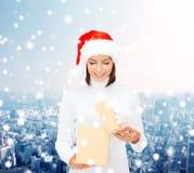 Le kvinnan i santa hjälpredahatt med gåvaasken Arkivfoton