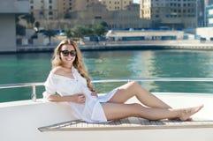 Le kvinnan i solglasögon som sitter på en yacht i Dubai Royaltyfria Bilder
