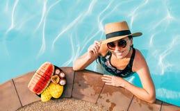 Le kvinnan i sugrörhatt i solglasögon som simmar, i pöl och att tycka om nya tropiska frukter arkivbilder
