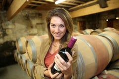 Le kvinnan i vinkällaren som rymmer en flaska av vin arkivfoto