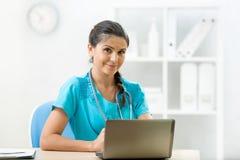 Le kvinnan manipulera sammanträde på skrivbordet i medicinskt kontor Royaltyfria Bilder