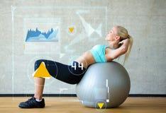 Le kvinnan med övningsbollen i idrottshall Fotografering för Bildbyråer