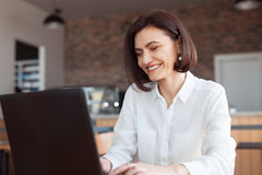 Le kvinnan med bärbara datorn i kafé Arkivfoto