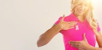 Le kvinnan med det rosa bandet som trycker på på bröstet fotografering för bildbyråer