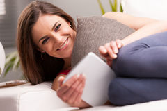 Le kvinnan med en minnestavla på hennes soffa fotografering för bildbyråer