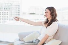 Le kvinnan med fjärrkontrollsammanträde på soffan arkivfoto