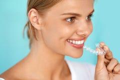 Le kvinnan med härligt leende genom att använda den osynliga tandinstruktören Arkivbilder