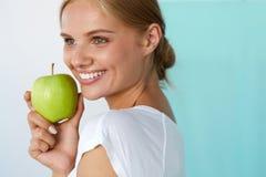 Le kvinnan med härligt leende, vita tänder som rymmer Apple Royaltyfri Foto