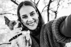Le kvinnan med hunden utomhus i höstdanandeselfie royaltyfria foton