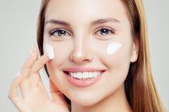 Le kvinnan med klar hud som applicerar fukta kräm, härlig kvinnlig framsidacloseup Skincare, skönhet och ansikts- behandling arkivbilder