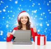 Le kvinnan med kreditkorten och bärbara datorn Arkivbild