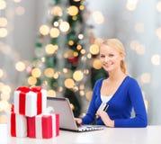 Le kvinnan med kreditkorten och bärbara datorn Arkivfoto